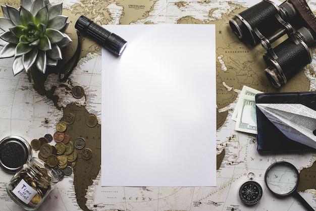 Papel en blanco con linterna y objetos de viaje