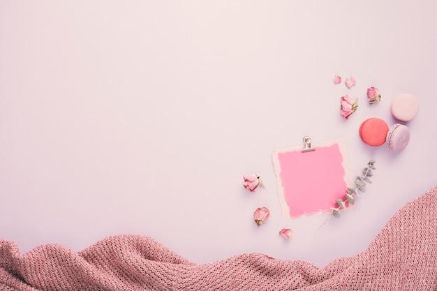 Papel en blanco con macarrones y pétalos de rosa.