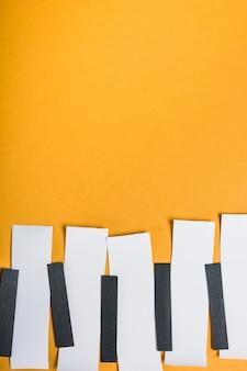 Papel blanco y negro dispuesto en fila haciendo teclas de piano sobre fondo amarillo