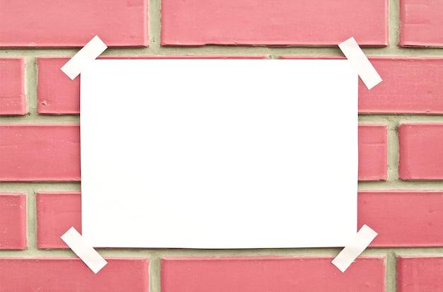 Papel en blanco en la pared de ladrillo