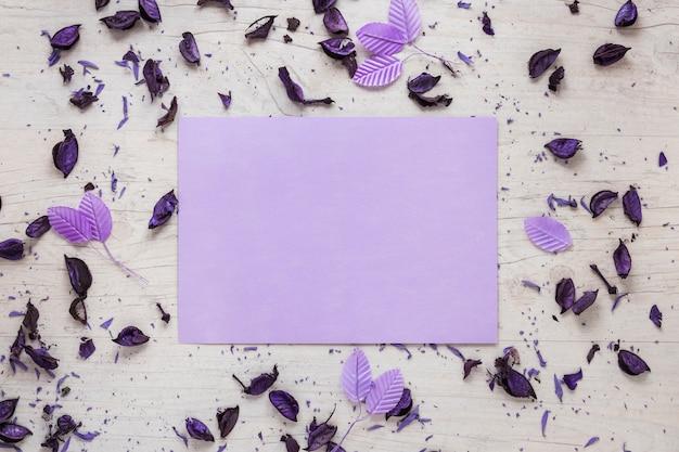 Papel en blanco con pétalos de flores y hojas en la mesa