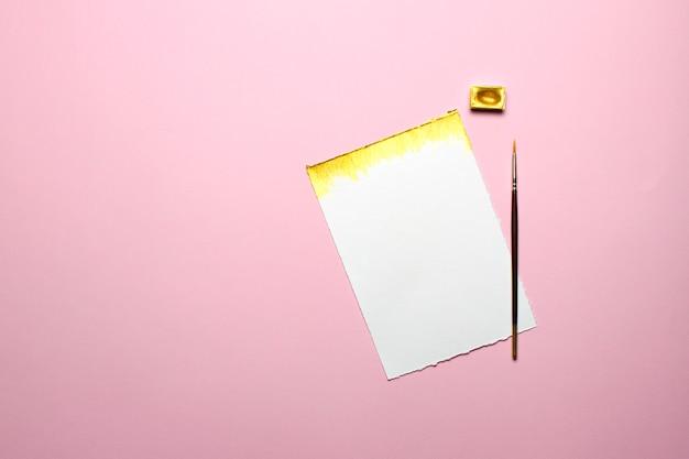 Papel en blanco con pintura dorada y pincel