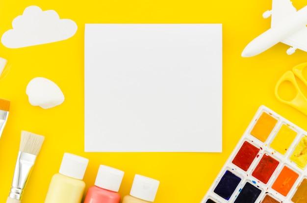 Papel en blanco con pinturas y avión de juguete