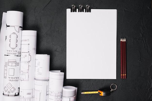 Papel en blanco con planos en la mesa