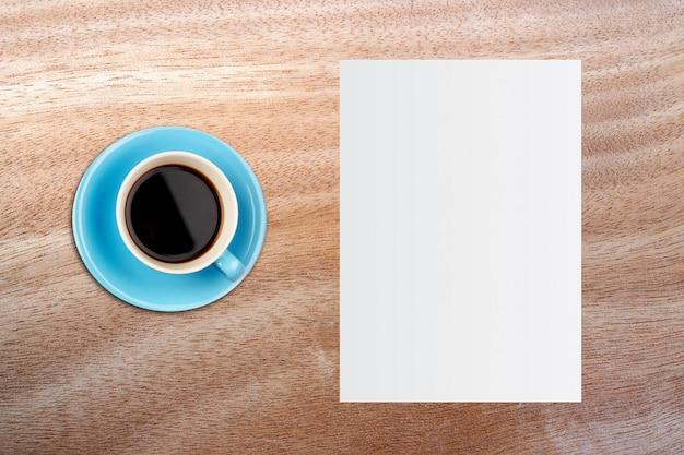 Papel blanco de la plantilla y taza de café sobre fondo de madera