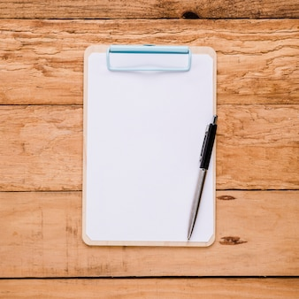 Papel en blanco en el portapapeles con bolígrafo sobre el escritorio de madera