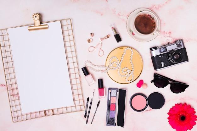 Papel blanco en el portapapeles; collar; gafas de sol; cámara; flor de gerbera; taza de café; collar y productos cosméticos sobre fondo rosa.
