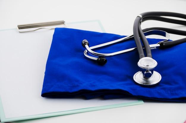 Papel blanco en el portapapeles; estetoscopio y guante quirúrgico sobre fondo blanco