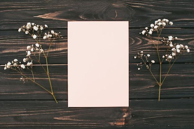 Papel en blanco con ramas de flores en la mesa
