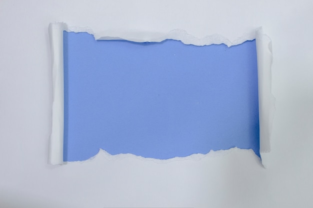 Papel blanco rasgado sobre fondo de color azul