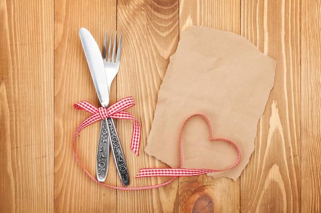Papel en blanco para receta o nota y cubiertos sobre fondo de mesa de madera