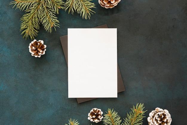 Papel en blanco rodeado de conos y hojas de pino