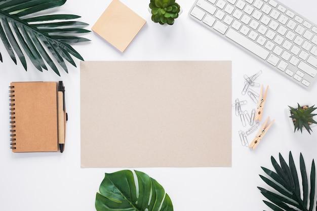 Papel en blanco rodeado de suministros de oficina en el espacio de trabajo blanco