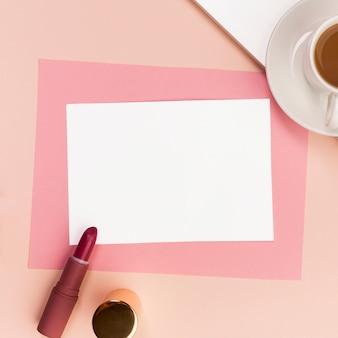 Papel blanco y rosa en blanco con lápiz labial, pincel de maquillaje y taza de café