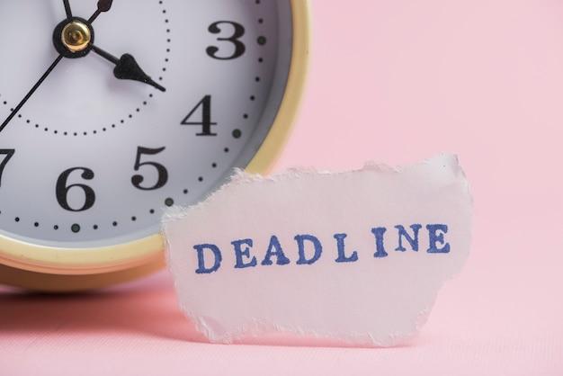 Papel blanco roto con texto de fecha límite cerca del reloj de alarma contra el fondo rosa