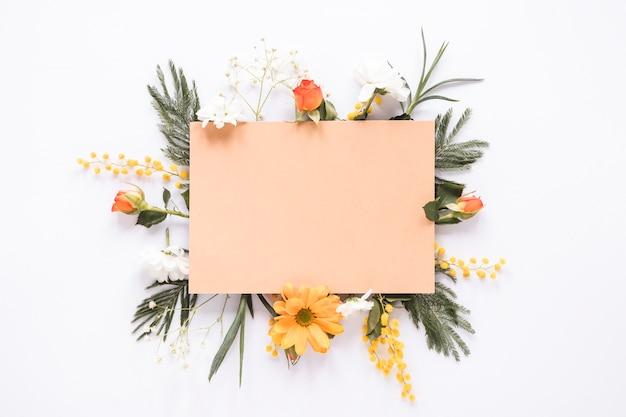 Papel en blanco sobre diferentes flores en la mesa