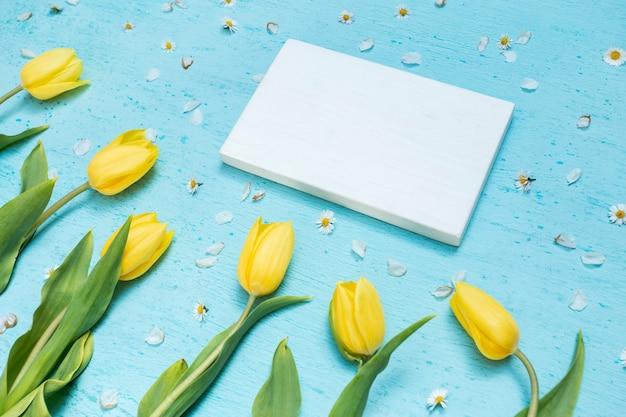 Papel en blanco y tulipanes amarillos