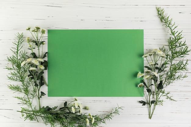 Papel en blanco verde con flores de crisantemo y hojas en el escritorio de madera blanco