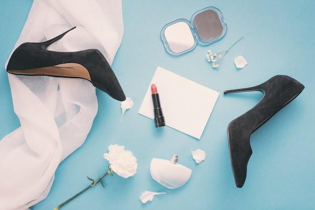 Papel en blanco con zapatos de mujer y lápiz labial en la mesa