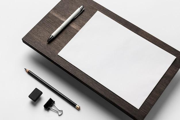 Papel y bolígrafo sobre soporte de madera