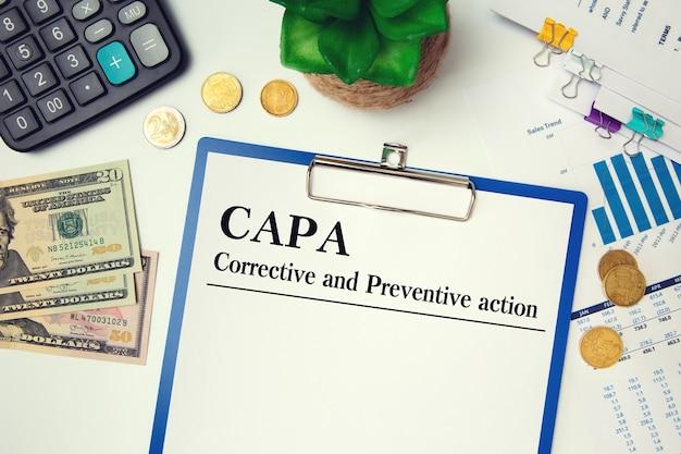 Papel con capa de acción correctiva y preventiva sobre la mesa, calculadora y vasos