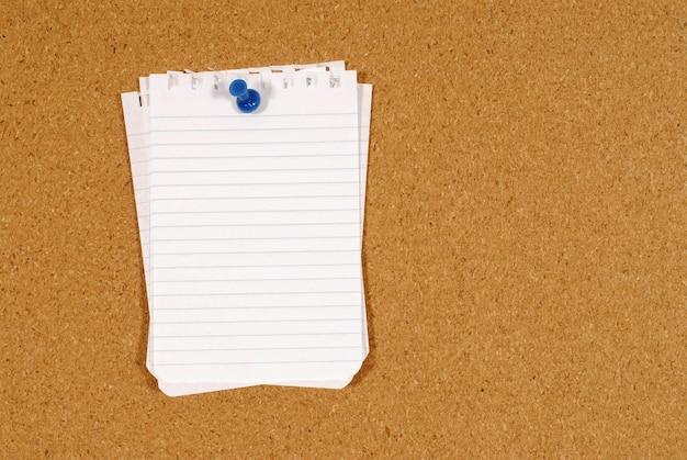 El papel de carta clavado en un tablero de corcho