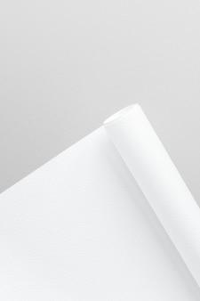 Papel de carta enrollado blanco en blanco sobre un fondo gris