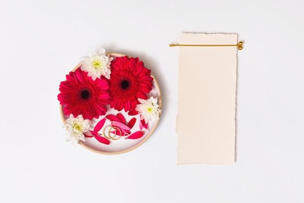 Papel cerca de anillos y conjunto de flores frescas en redondo.