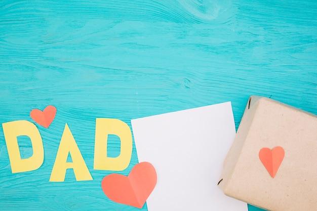 Papel cerca de caja, corazones rojos y título de papá.