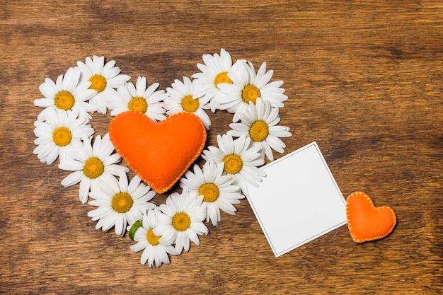 Papel cerca de corazón ornamental de flores blancas y juguetes naranjas.