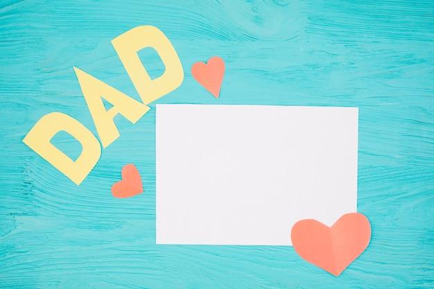 Papel cerca de corazón rojo y título de papá
