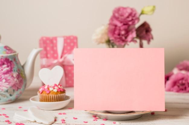 Papel cerca de delicioso pastel, caja de regalo y tetera.