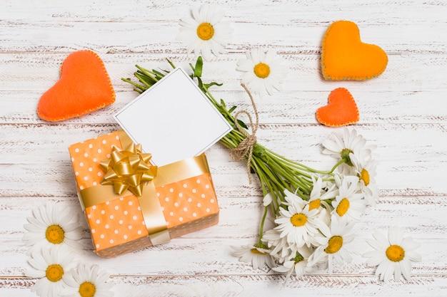 Papel cerca del presente, ramo de flores y corazones decorativos.