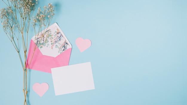 Papel cerca de sobre, corazones decorativos y planta.
