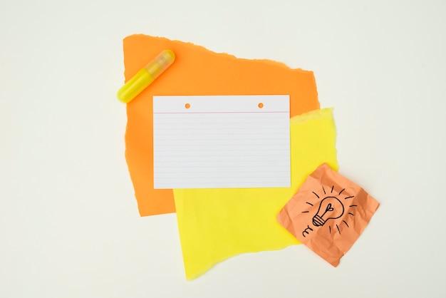 Papel de color y pegamento con bombilla dibujada a mano nota papel aislado sobre fondo blanco.