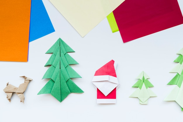 Papel colorido y árbol de navidad hecho a mano; reno; papá noel origami de papel aislado sobre fondo blanco