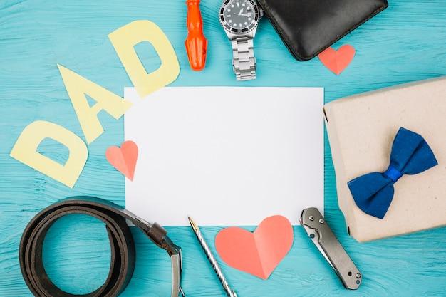 Papel entre corazones rojos y título de papá cerca de accesorios masculinos.