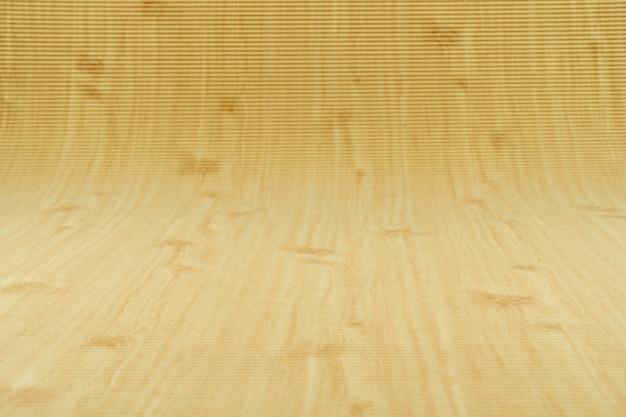 Papel corrugado con curva de fondo de patrón de madera en el conner al fondo infinito.