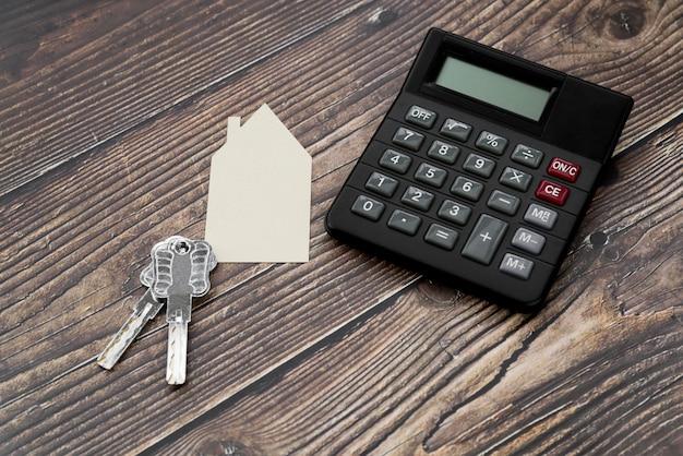 Papel cortado casa con llaves y calculadora en superficie con textura de madera