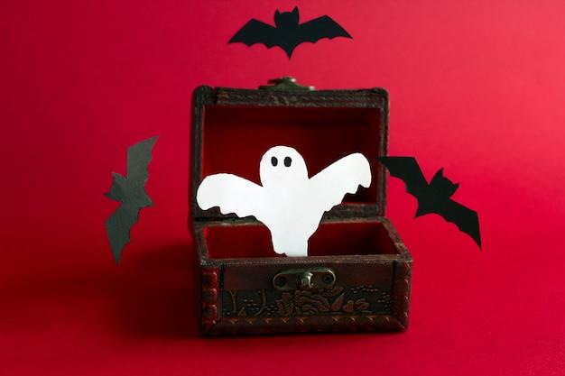 Papel cortado fantasma aterrador y murciélagos vuelan de un viejo cofre de madera vintage