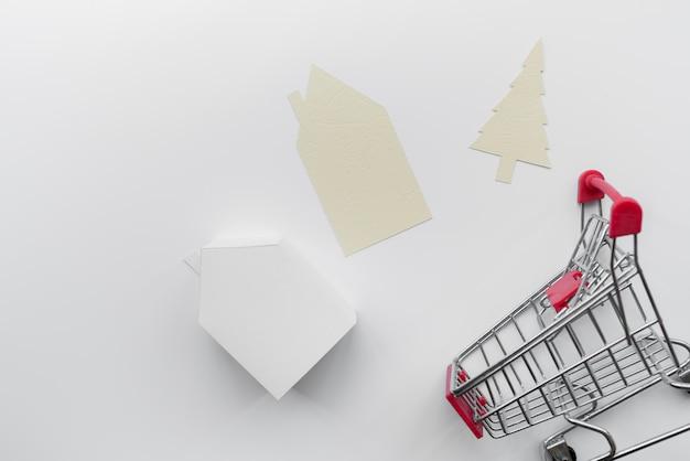 El papel cortó la casa y el árbol de navidad con el modelo miniatura de la casa y el carro de compras aislados en el fondo blanco