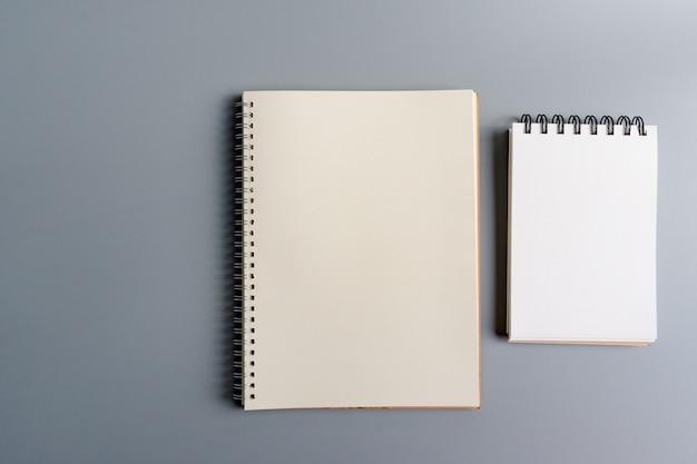 Papel de cuaderno abierto en blanco sobre gris, equipo de oficina, papelería escolar y concepto de educación