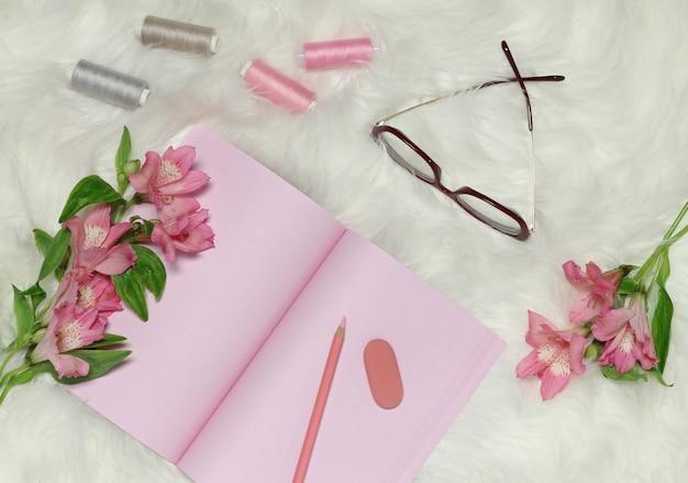 Papel de cuaderno rosa sobre fondo blanco peludo con flores rosadas y lentes rojos