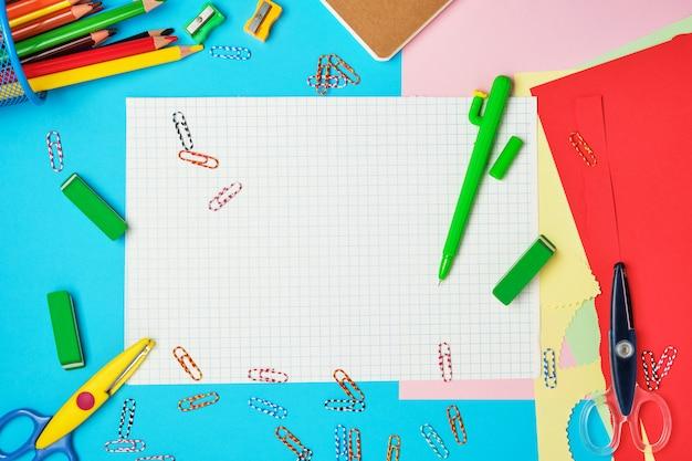 Papel cuadrado blanco de cuadernos, lápices de colores de madera, clips de papel, tijeras