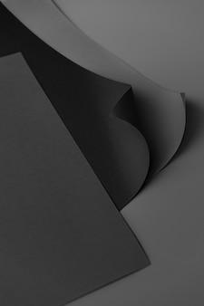 Papel cuadriculado negro rizado sobre un fondo gris oscuro