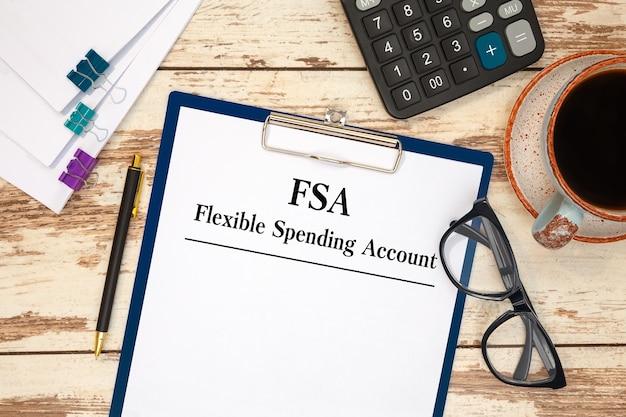 Papel con la cuenta de gastos flexible fsa en la mesa, calculadora y anteojos