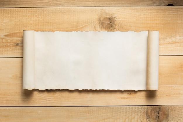Papel curvo o enrollado sobre textura de fondo de madera