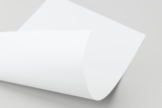 Papel doblado en blanco sobre un fondo gris