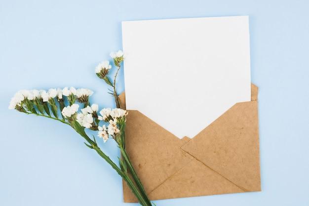 Papel en blanco blanco en el sobre marrón con flores blancas sobre fondo azul