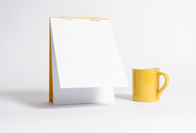 Papel espiral calendario en blanco y taza amarilla para la plantilla de maqueta